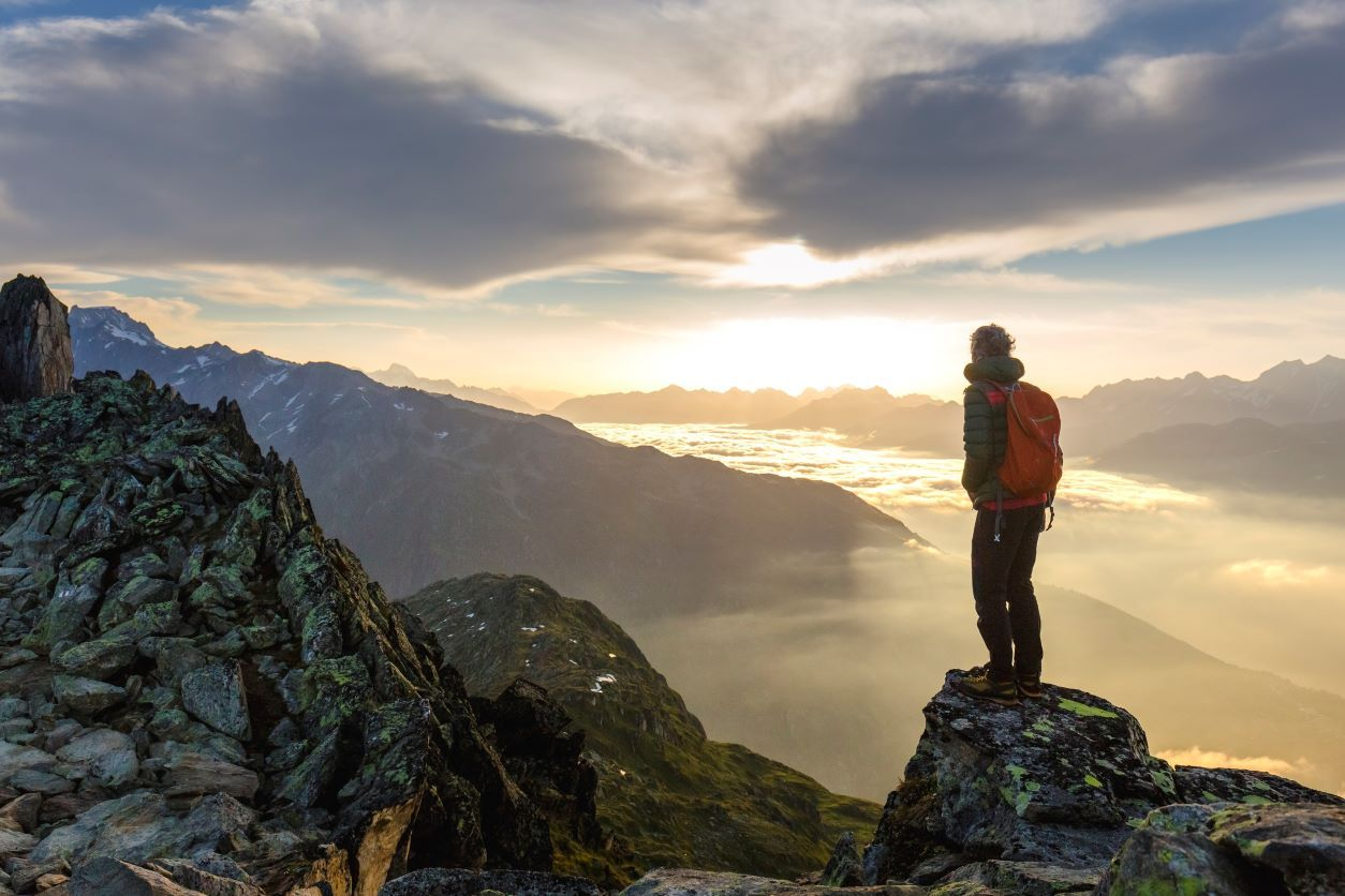 11Man standing on a mountain top looking out at a sunrise