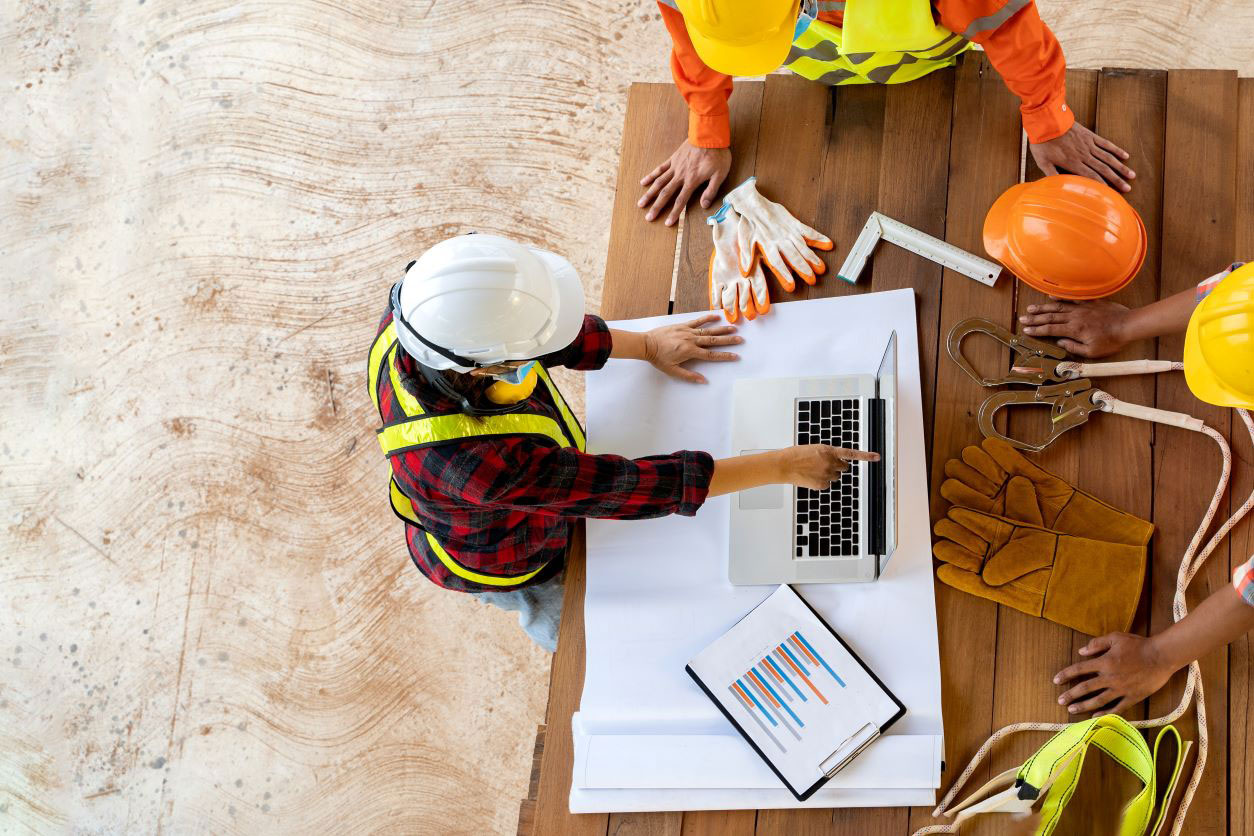 11Group of construction workers planning around laptop