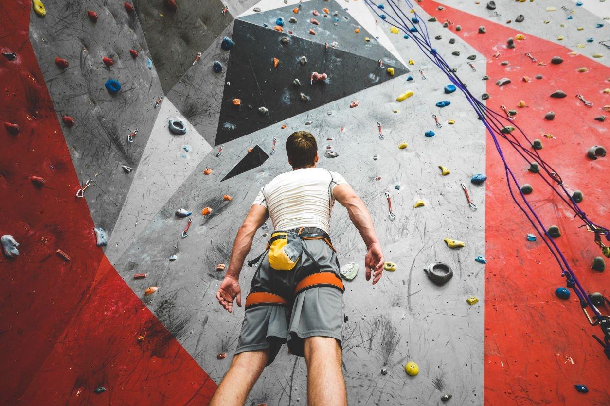 11Man looking up a rock climbing wall