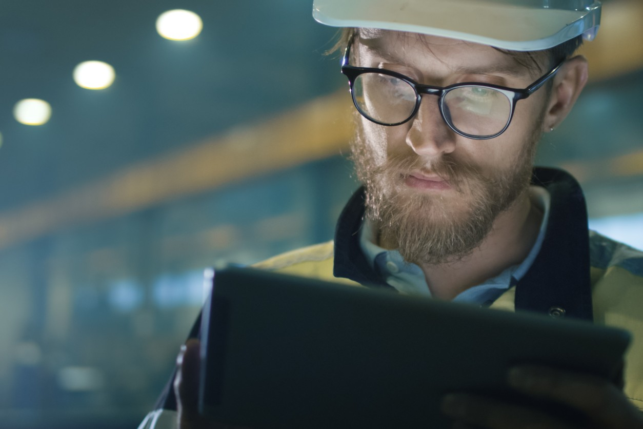11Technician looking at tablet in industrial setting