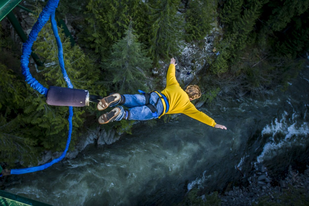 11Young man bungee jumping over river
