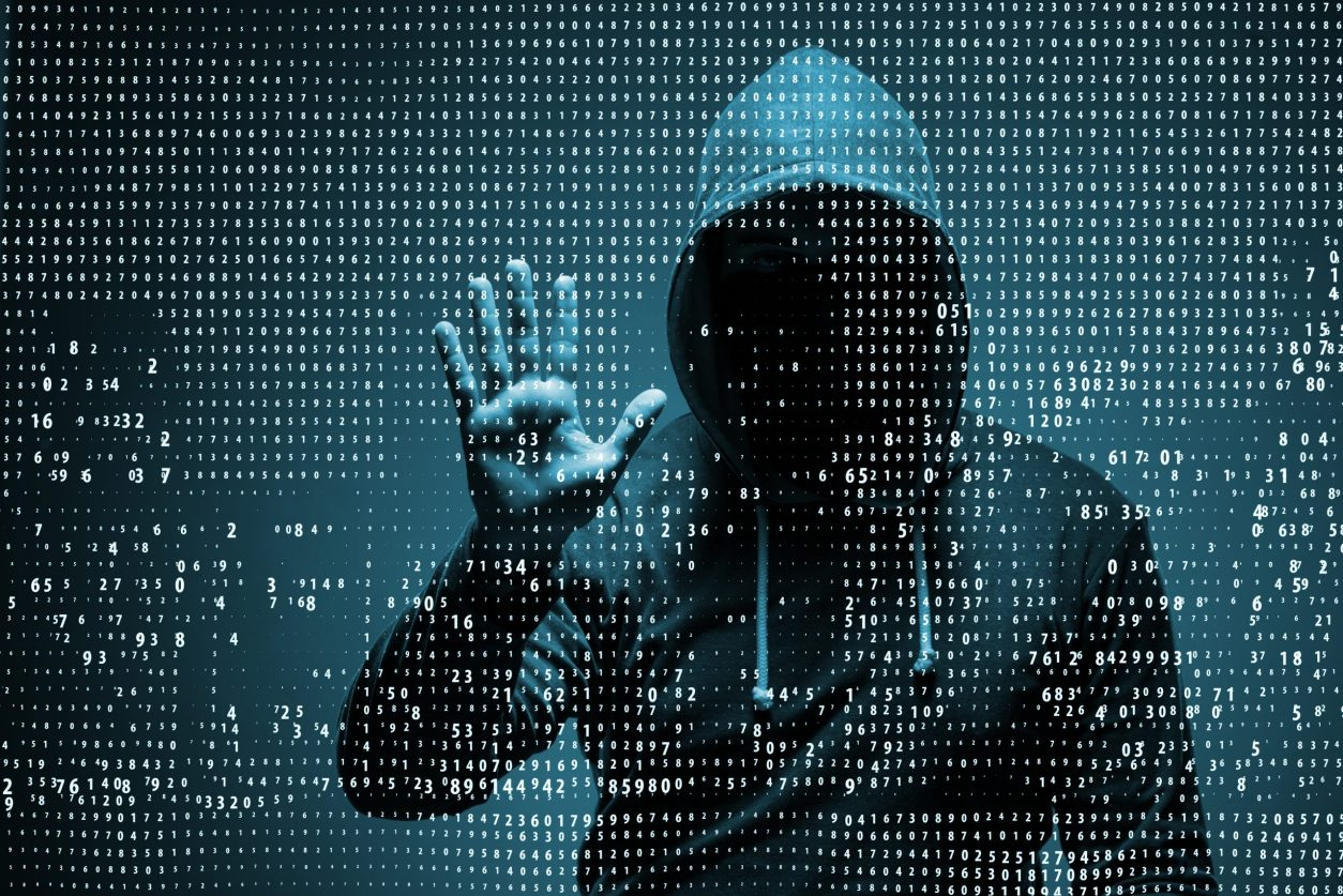 11Cyber attack hacker with hand up against a digital display
